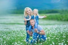 roligt lyckligt ha för familj utomhus Stående av den lyckliga familjen i lyckligt folk för bygd som bär utomhus jeans som tycker  Arkivbilder