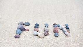 Roligt ord som göras av kiselstenar på en sandig strand Arkivbild