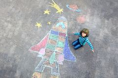Roligt pojkeflyg för liten unge i universum vid en rymdfärjabildmålning med färgrika chalks Idérik fritid för royaltyfri bild