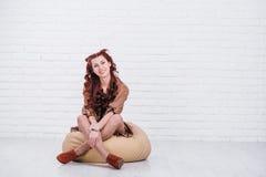 Roligt rött hårflickasammanträde på kudden Royaltyfri Foto