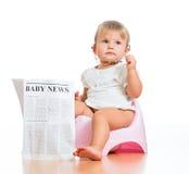 Roligt sitta barnvakt på chamberpot med tidningen Arkivbild