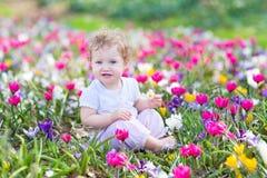 Roligt skratta behandla som ett barn att spela med första vårblommor Royaltyfria Bilder