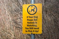 Roligt tecken som påminner fotvandrare att plocka upp efter deras hundkapplöpning royaltyfria foton