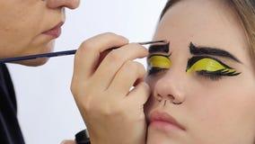 Roligt tecknad filmsmink yrkesmässig makeupkonstnär som gör komiskt smink för popkonst