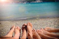 Roligt turismbegrepp med fot av turister som ligger på sand royaltyfri fotografi