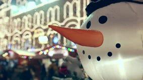 Roligt uppblåst snögubbehuvud med suddiga ljus på bakgrund arkivfilmer