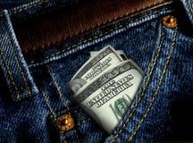 ROLKA 100 DOLAROWYCH rachunków WKŁADAJĄCYCH W niebieskich dżinsy WKŁADAĆ DO KIESZENI zbliżenie obraz stock
