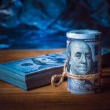 Rolka dolary z paczką dolary na tle textured drewniane deski w błękita świetle fotografia royalty free