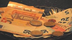 Rolka materiał filmowy opuszcza puszek euro monety na papierowym pieniądze w ciemnego brązu szklanym talerzu zbiory wideo