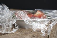 Rolka opakunkowy plastikowy rozciągliwość film nad talerzem vegetabes zakończenie na drewnianym tle Żadny plastikowy pojęcie Zero fotografia royalty free