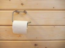 Rolka papieru toaletowego obwieszenie na właścicielu z drewnianą ścianą Zdjęcia Royalty Free