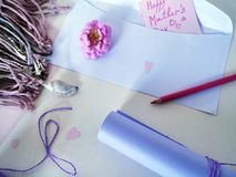 Rolka pozafioletowy papier, biała koperta, czerwony ołówek i pastelowa kredka dla gratulacj na Macierzystym ` s dniu, Obraz Royalty Free