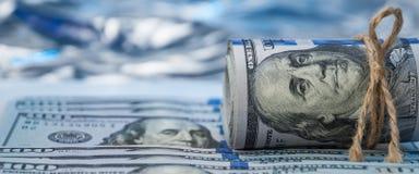Rolka rachunki sto dolarów wiążących z arkaną kłama na rozrzuconych rachunkach zdjęcia royalty free