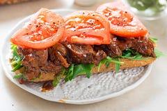 Rolka z grill wołowiny brisket na rakieta pomidorach i liściach fotografia stock