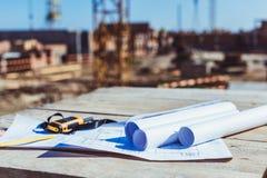 Rolki papier z budynków planami i przenośny radio na drewnianej powierzchni zdjęcie stock