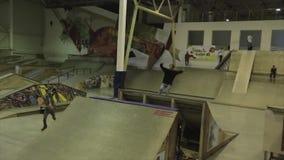 Rolkowa łyżwiarka robi 180 trzepnięciu w powietrzu trampolina ekstremum sztuczka Rywalizacja w skatepark zbiory wideo