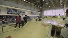 Rolkowa łyżwiarka skacze od trampoliny, chwytów przecinający cieki w powietrzu ekstremum Rywalizacja w skatepark zbiory