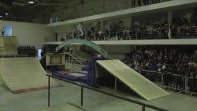 Rolkowe łyżwiarek rolki na wyginającym się łuku między trampolinami ekstremum Rywalizacja w skatepark ludzie zbiory