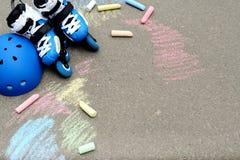 Rolkowe inline łyżwy z hełmem w łyżwa parku na szarość asfalcie malującym barwiącym piszą kredą tło Zdjęcie Royalty Free