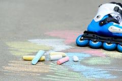 Rolkowe inline łyżwy z hełmem w łyżwa parku na szarość asfalcie malującym barwiącym piszą kredą tło Fotografia Stock