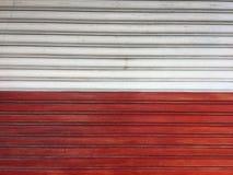Rolkowy drzwiowy biały i czerwony kolor, żaluzi tekstury drzwiowy tło fotografia stock