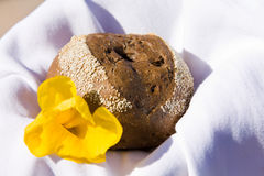 Roll. Bun and yellow flower on a white napkin Stock Images