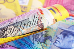Australian Currency. A roll of Australian currency over a currency background stock images