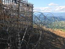 Roll of barbed wire at land boarder on the mountain for military. Safety and protection Stock Photo