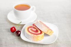 Roll with berries cherry on plate and cap of tea Royalty Free Stock Photo