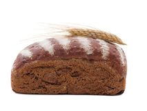 Roll of black bread with wheat ear top close-up on a white isolated background. Side view. Roll of black bread with white stripes of flour top with wheat ear top royalty free stock photos