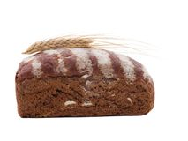 Roll of black bread with wheat ear top on a white isolated background. Side view. Roll of black bread with white stripes of flour top with wheat ear top on a royalty free stock photography