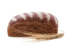 A roll of black bread with wheat spike in front of it on a white isolated background. Side view. A roll of black bread with white stripes on top with a wheat stock photography