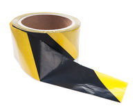 Roll of black yellow caution tape isolated Royalty Free Stock Photo