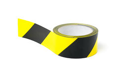 Black and yellow caution tape. Roll of black and yellow caution tape on a white background royalty free stock photos