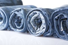 Roll blue denim jeans arranged in line. Isolated on white royalty free stock image