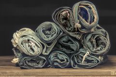 Roll blue denim jeans arranged in stack.On oak wood texture background,.Ripped jeans of a stack Hipster fashion copy space for tex royalty free stock photography