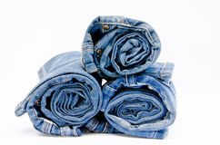 Roll blue denim jeans arranged in stack. On white background stock photography