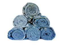 Roll blue denim jeans arranged on white background Stock Photos