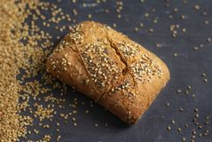 Roll bread with poppy and sesame seeds on dark background royalty free stock image