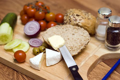 Roll and butter. Making a breakfast roll, spreading butter, breakfast products on wooden chopping board royalty free stock photos