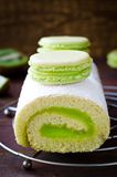 Roll cake with kiwi cream decorated macarons Royalty Free Stock Photography