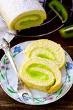 Roll cake with kiwi cream decorated macarons Stock Image