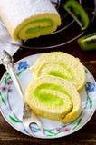Roll cake with kiwi cream decorated macarons Stock Image