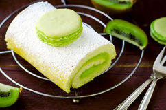 Roll cake with kiwi cream decorated macarons Royalty Free Stock Images