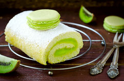 Roll cake with kiwi cream decorated macarons Royalty Free Stock Image