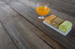 Roll cake with orange juice on a wood background. Royalty Free Stock Photography