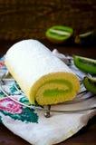 Roll cake witn kiwi cream decorated macarons Royalty Free Stock Photos