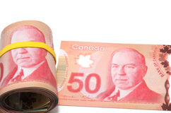 Roll of 50 Canadian dollars. Series of Canadian dollars with yellow rubber band over the eyes Stock Image