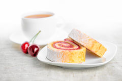 Roll with cherries on plate and cap of tea Stock Images