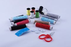 Sewing equipment. Roll of color threads, needle, measuring tape and white Stock Images